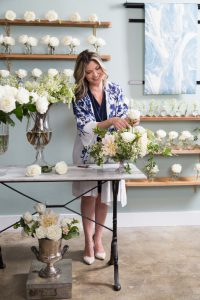 A florist works on an arrangement in a flower shop. She is adjusting flowers in a vase. All the flowers in the photo are white, there are several different types. She wears heels, a dress and a long flowing blue and white shawl. She is expressing positivity and looking at her work.